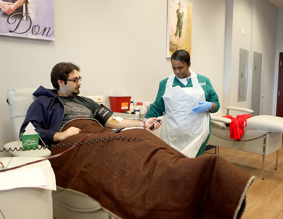 Jeremy Majewski of Geneva is helped by phlebotomist and team leader Shamone Lake as he donates platelets at the Heartland Blood Center in Geneva Monday.
