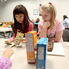 Sandra Bach (left) and Arianna Failor, members of Brownie Troop 4106, learn how to make a cash transaction in anticipation of Girl Scout cookie sales during their meeting at the Sugar Grove Library.