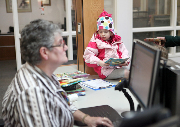 Four-year-old Averie Criss of Sugar Grove waits with her mom and siblings (not pictured) as Michelle Drawz, circulation services managers, helps them check out books at the Sugar Grove Library. The library now has expanded its days of operation to include Sunday and Monday.