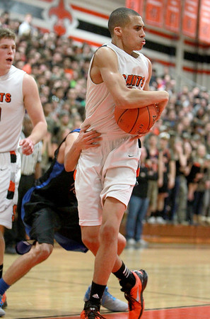 St. Charles East's A.J. Washington grabs a rebound during their home game against St. Charles North Friday night.