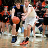St. Charles North's Quinten Payne (left) and St. Charles East's James McQuillan go after a loose ball during their game at East Friday night.