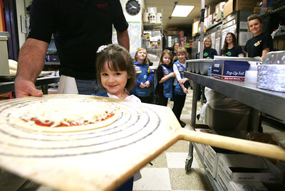 Monica Maschak - mmaschak@shawmedia.com Daisy girl scout Evie Howell carries her personal cheese pizza to the oven to be baked at Jimano's Pizzeria in Fox River Grove on Wednesday, January 23, 2013. The girls from girl Scout troop 1206 from Cary went to the pizza shop to learn about making pizza and each girl went home with her own pizza creation.