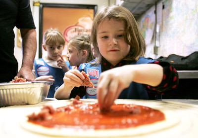 Monica Maschak - mmaschak@shawmedia.com Simone Kidder, of girl scout troop 1206, places sausage on her personal pizza at the Jimano's Pizzeria in Fox River Grove on Wednesday, January 23, 2013. Each girl went home with her own pizza creation.