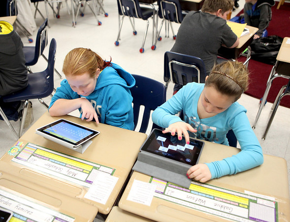Alice Gustafson Elementary School fifth graders Molly Schuster and Gabbie Watson use their iPads for a project Wednesday.
