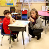 Teacher Meg Bingham crouches next to Andrew Pasker's desk during a class at the Mades-Johnstone Center in St. Charles.