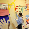 Fifth grader Noah Uher paints part of a mural on the wall at the Mades-Johnstone Center in St. Charles.
