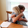 Tanner Saunders, 15, gives his sister, Franki Walsh, 6, a hug during a tutoring session in the kitchen of his Campton Hills home. Tanner suffers from complex regional pain syndrome.