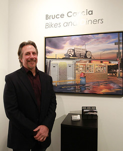 Sarah Minor — sminor@shawmedia.com Bruce Cascia stands next to his painting of Hamburger Heaven at and art opening at the Elmhurst Art Museum on Friday, Jan. 25.