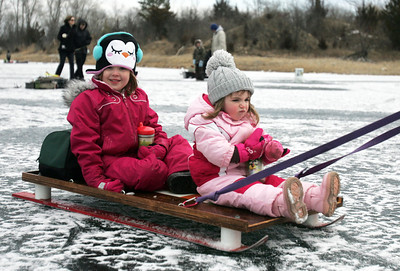 Monica Maschak - mmaschak@shawmedia.com Izzy Mulvey, 4, and Josie Mulvey, 2, enjoy getting pulled along on the ice of Atwood Lake by their father during the Frosty Fishing Fair at The Hollows Conservation Area on Saturday, January 5, 2013.  Matt Mulvey brought his daughters to the event to try to get them interested in ice fishing.