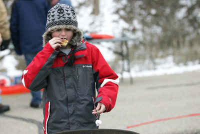 Monica Maschak - mmaschak@shawmedia.com Charlie Marsh, 11, warms up by the fire and roasts marshmallows after coming off the ice from his first ice fishing experience at the Frosty Fishing Fair on Saturday, January 5, 2013.