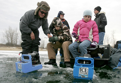 Monica Maschak - mmaschak@shawmedia.com Park Ranger Chad Secor (left) helps Hunter White, 9, and Elise White, 10, cast their line into the frozen lake for their first ice fishing experience during the Frosty Fishing Fair at The Hollows Conservation Area on Saturday.