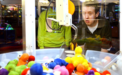 Monica Maschak - mmaschak@shawmedia.com Michael Clear (right) plays an arcade game as his peer buddy Chris Juliano watches at the Brunswick Zone in Algonquin on Thursday, November 15, 2012.  The Best Buddies club at Crystal Lake South, where peer buddies are matched with special needs students, tries to have monthly outtings for the kids to hang out and have fun together.  © Northwest Herald