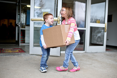 Josh Peckler - jpeckler@shawmedia.com Parker Justen, 4 and sister Maddie, 7 smile as they carry a box out of Chauncey H. Duker School in Mchenry to be loaded on a semi-trailer filled with donated clothes collected to help the families who lost their homes from a fire. © Northwest Herald