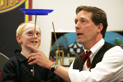 Monica Maschak - mmaschak@shawmedia.com Michael Kett (right), also known as Professor Marvel, helps Tommy Stocker, 8, juggle a plate on a stick for the opening act of Professor Marvel's Amazing Flea Circus at the McHenry Public Library on Friday, January 4, 2013.  © Northwest Herald
