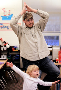 "Sarah Nader - snader@shawmedia.com T.J. Schock of Woodstock and his daughter, Emma, 3, try different yoga positions while attending Guy's Night Out at Verda Dierzen Learning Center in Woodstock on Thursday, January 17, 2013. Pre-K and kindergartens brought their ""favorite big guys"" for throwing and catching games, jumping, hopping and balancing activities along with yoga ."
