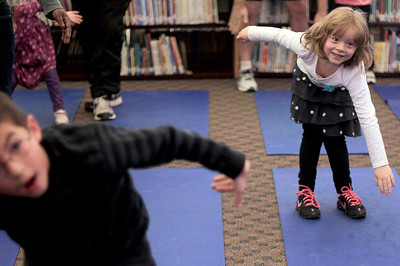 "Sarah Nader - snader@shawmedia.com Mada Jo Thomas, 6, of Woodstcok does yoga during Guy's Night Out at Verda Dierzen Learning Center in Woodstock on Thursday, January 17, 2013. Pre-K and kindergartens brought their ""favorite big guys"" for throwing and catching games, jumping, hopping and balancing activities along with yoga ."