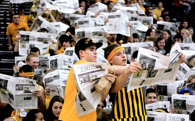 Sarah Nader - snader@shawmedia.com Matt Hickey (left), 18, of Carpentersville holds up a newspaper while the Jacobs' starting line up is called during Tuesday's game in Algonquin.