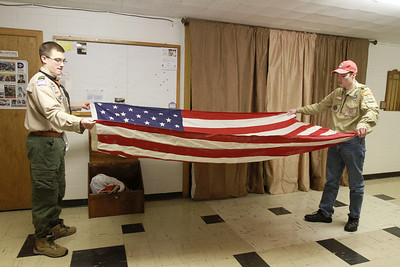 Matt Walden (left) is assisted by his brother Ray Walden IV in folding a flag that was left at the Berwyn VFW to be retired. Sarah Minor — sminor@shawmedia.com
