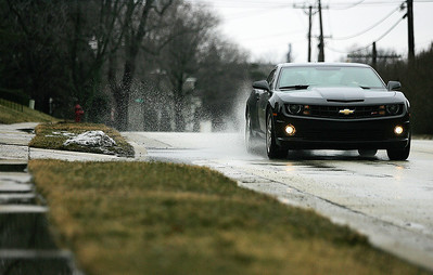 Monica Maschak - mmaschak@shawmedia.com A car drives into a puddle on Lake Avenue in Woodstock on Monday, January 28, 2013. According to AccuWeather.com, temperatures peaked at 48 degrees on Monday, allowing a majority of the snow and ice in the county to melt overnight.