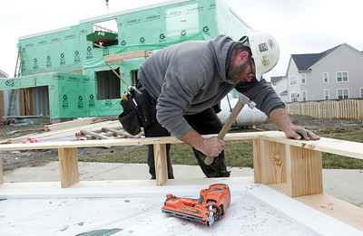 H. Rick Bamman - hbamman@shawmedia.com Carpenter Brian Gordon of Burlington, Wisconsin attaches exterior trim while working on a house Monday on Caldwell Drive in the Coventry Lakes subdivision in Lake in the Hills. Crews were taking advantage of the spring-like weather to work on several new homes.