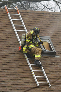 H. Rick Bamman - hbamman@shawmedia.com A firefighter clears glass from a skylight while venting the second floor of a home at 1430 Cary Algonquin Rd.