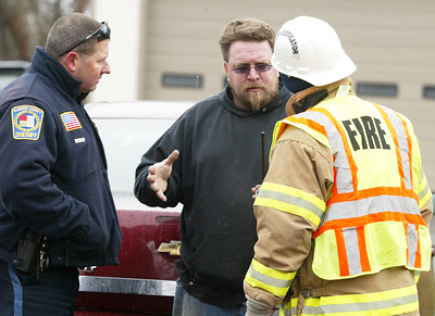 H. Rick Bamman - hbamman@shawmedia.com Homeowner Ed Killroy (center) speaks with a fire department investigator Wednesday. Kilroy evacuated the house once he heard the fire alarms. He was not injured.