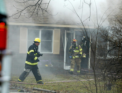 H. Rick Bamman - hbamman@shawmedia.com Firefighters battle a house fire at 1430 Cary Algonquin Rd. Wednesday, January 30, 2013.