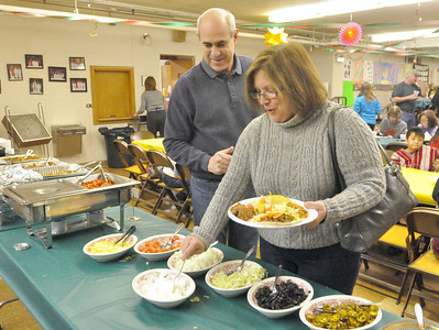 """John and Kathy Dudek, of Riverside, help themselves to taco fixings. Ascension Lutheran Church in Riverside holds a """"Resettle a Refugee"""" benefit featuring a do-it-yourself taco bar on Saturday, Jan. 26, 2013. Proceeds benefit RefugeeOne, whose mission is to resettle refugees in the Chicago area. Bill Ackerman — backerman@shawmedia.com"""