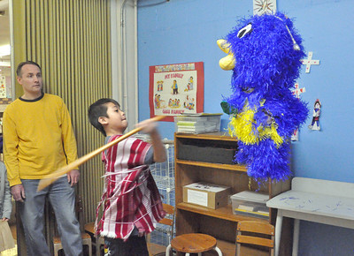 """Yu Eh, 13, of Chicago, takes a wack at a pinata at Ascension Lutheran Church of Riverside's """"Resettle a Refugee"""" benefit featuring a do-it-yourself taco bar on Saturday, Jan. 26, 2013. Proceeds benefit RefugeeOne, whose mission is to resettle refugees, like Yu Eh, from Burma, in the Chicago area. Bill Ackerman — backerman@shawmedia.com"""
