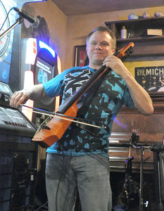 Tom Culver steps away from his day job as a music educator at La Grange School District 102 to play the electric cello with his band, Strung Out, at the The Kerry Piper, in Willowbrook, on Friday night, Jan. 11, 2013. Bill Ackerman — backerman@shawmedia.com