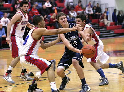 Monica Maschak - mmaschak@shawmedia.com Cary-Grove Trojan Jason Gregoire, surrounded by Dundee-Crown Chargers, passes the ball in an opening during the game on Friday, January 25, 2013.  The Chargers won 52-39.