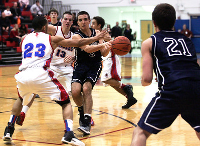 Monica Maschak - mmaschak@shawmedia.com Tyler Szydlo, for the Trojans, passes the ball to teammate Ian May in the last period of the game at Dundee-Crown High School on Friday, January 25, 2013.  The Trojans lost 52-39.