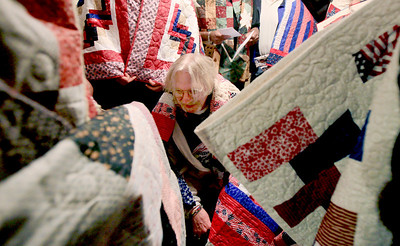 Sarah Nader - snader@shawmedia.com Veteran Patrick Zahnle (center) of Hebron is surrounded by quilts while the veterans all look at their homemade quilts that were donated by the Huntley Quilts of Valor group to the veterans at Transitional Living Services in Hebron on Thursday, January 10, 2013.  Two months ago the group didn't think they would have enough money to keep quilting for veterans in 2013. They have since received more donors and will be quilting for another year.