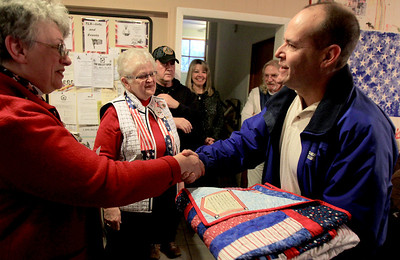Sarah Nader - snader@shawmedia.com Jan Meyer (left) of Huntley hands veteran Larry Posner of Hebron a quilt at Transitional Living Services in Hebron on Thursday, January 10, 2013. The Huntley Quilts of Valor group made 20 quilts for the veterans at TLS.