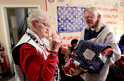 Sarah Nader - snader@shawmedia.com Sue Bruss (left) of Huntley hands veteran Patrick Zahnle of Hebron a quilt at Transitional Living Services in Hebron on Thursday, January 10, 2013. The Huntley Quilts of Valor group made 20 quilts for the veterans at TLS.