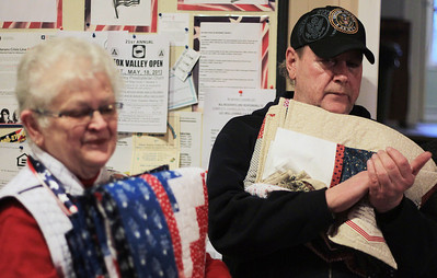 Sarah Nader - snader@shawmedia.com Sue Bruss (left) of Huntley hands veteran Don Lindguist of Hebron a quilt at Transitional Living Services in Hebron on Thursday, January 10, 2013. The Huntley Quilts of Valor group made 20 quilts for the veterans at TLS.
