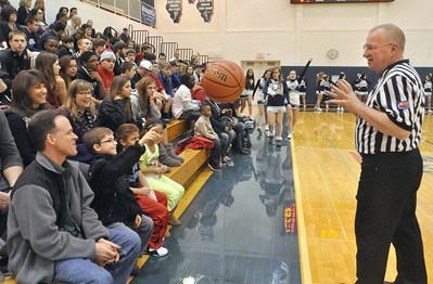 Alex Gansberg, 8, of Lisle, tosses back the ball he was holding for referee Johnny Garcia so the Lisle - Walther Lutheran varsity boys basketball can get started on Monday, Jan. 28, 2013 in Lisle. Bill Ackerman — backerman@shawmedia.com