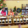 Gabby's Wine Den employee Patti Anselme assists Mike Bila, left, as he picks out a gift for his brother at Gibby's Wine Den in Geneva Dec. 31. <br /> <br /> (Rena Naltsas photo for the Kane County Chronicle)