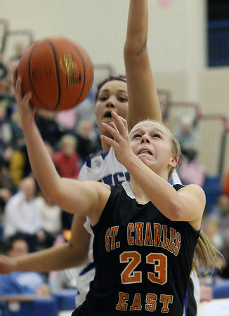 St. Charles East's Amanda Hilton goes up for a shot while Geneva's Sidney Santos attempts a block from behind during Friday's game in Geneva.<br /> (Jeff Krage photo for the Kane County Chronicle)