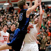 Erik Miller of St. Charles North tries to get a shot past Dom Adduci of St. Charles East during their game at East Friday night.(Sandy Bressner photo)