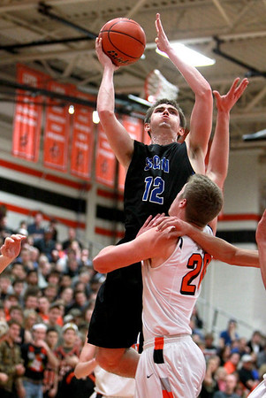 Quinten Payne of St. Charles North tries to get a shot past Tyler Windau of St. Charles East during their game at East Friday night.(Sandy Bressner photo)