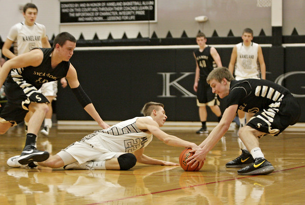 Kaneland's Dan Miller (22) and Sycamore's Ben Niemann struggle for possession of a ball during the third quarter in Maple Park, Ill., Tuesday, Jan. 22, 2013. Kaneland defeated Sycamore, 43-42. (Rob Winner photo)