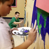 Fifth graders Jalen Green (left) and Devon Horne paint part of a mural on the wall at the Mades-Johnstone Center in St. Charles. (Sandy Bressner photo)