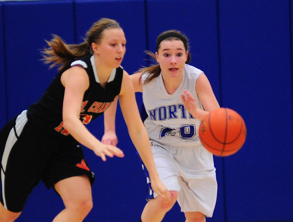 Sam Novak of St. Charles North and Laney Deckrow of St. Charles East compete for the loose ball at North High School Saturday, Jan. 12.  (Rena Naltsas photo for the Kane County Chronicle)