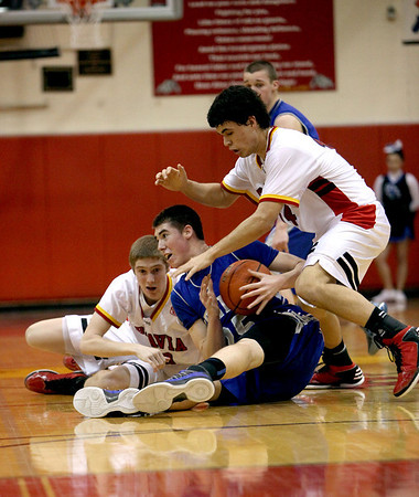 Geneva's Nate Navigato (center) fights for the ball against Batavia's Tucker Knox (far left) and Micah Coffey during their game at Batavia Friday night.(Sandy Bressner photo)