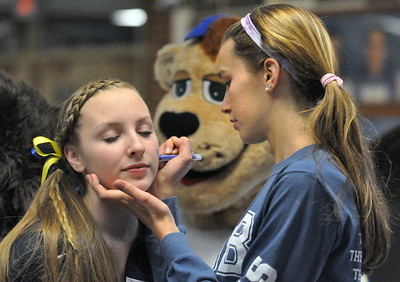 """Sophomore Colette Kocek, of La Grange Park, gets her cheek decorated by Caroline Walsh, of La Grange Park. Lyons Township holds a """"Pack the Place"""" event with back to back girls and boys basketball games, with fundraising by LT school organizations on Saturday, Jan. 26, 2013. Bill Ackerman — backerman@shawmedia.com"""
