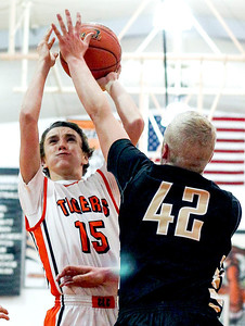 Sarah Nader- snader@shawmedia.com Crystal Lake Central's Derek Olson (left) shoots over Grayslake North's Nate Dodge during the second quarter of Friday's home game January, 3, 2014. Grayslake North defeated Crystal Lake Central, 71-50.
