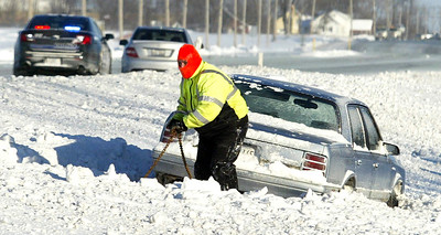 "H. Rick Bamman -hbamman@shawmedia.com A worker from Whitey's Towing hooks up one of the vehicles that slid off of Randall Rd. north of Huntley Rd. Monday. Northbound traffic was closed at Randall and Huntley roads and southbound traffic was closed at Randall Road and Corporate Parkway until salt trucks arrived. Officers described the roads as ""sheets of ice."""