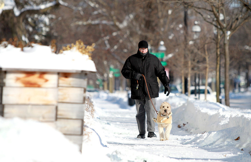 Mike Orlando walks his dog, Jackpot, in below zero temperatures through downtown Geneva Monday morning.