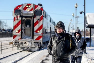 Sarah Nader- snader@shawmedia.com College student Matt Marten (left) of Cary and David Badillo of Chicago wait for the inbound Metra train at the Cary station Tuesday, January 7, 2014. Snow and ice-packed railroad switches along with the number of hours railroad employees can work are causing delays, cancellations and headaches for Metra commuters.